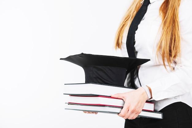 Mujer de cultivo con libros y gorra académica