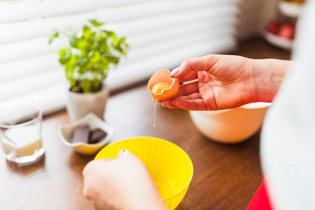 Mujer de cultivo poniendo huevos crudos en un tazón