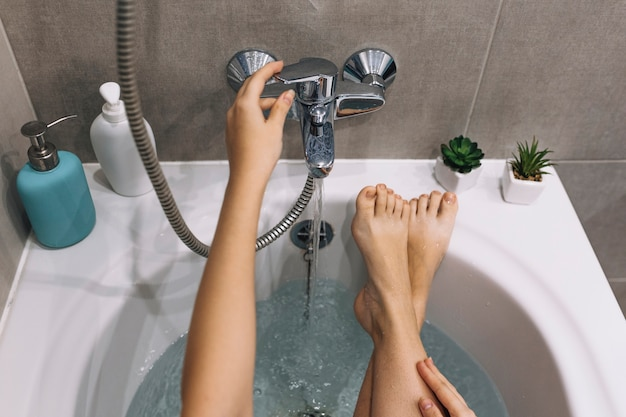Mujer de cultivo relajante en el baño