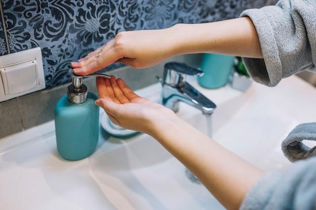 Mujer de cultivo vertiendo jabón en la mano