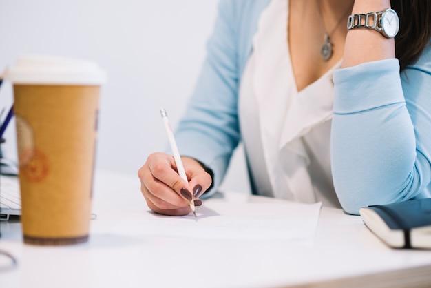 Mujer de cultivos escribiendo en la oficina