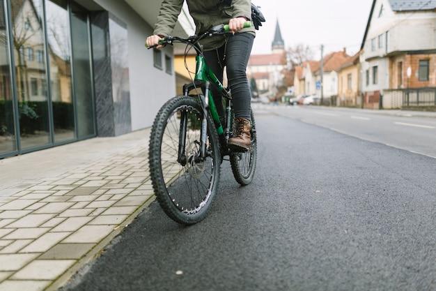 Mujer de cultivos montando bicicleta