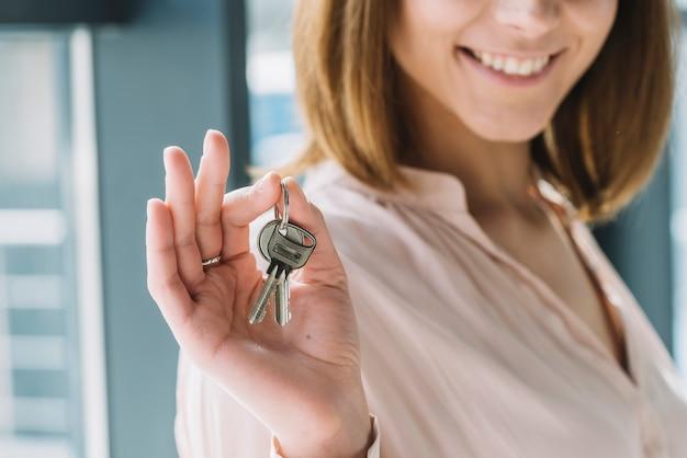 Mujer de cultivos mostrando llaves