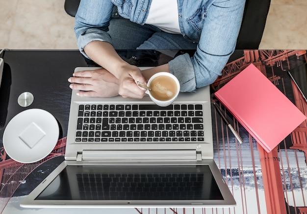 Mujer de cultivos tomando una bebida caliente y usando una computadora portátil trabajando de forma remota