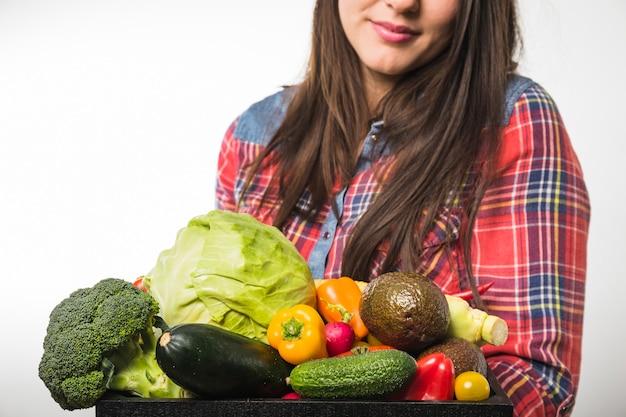 Mujer de cultivos con varios vegetales