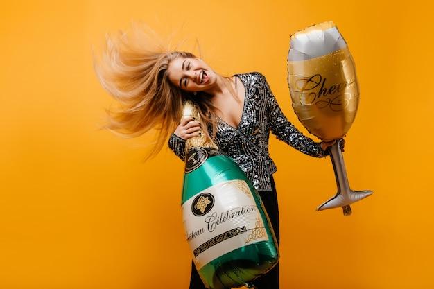 Mujer de cumpleaños emocionada bailando con botella de champán. retrato de mujer emotiinal positiva jugando después de la fiesta.