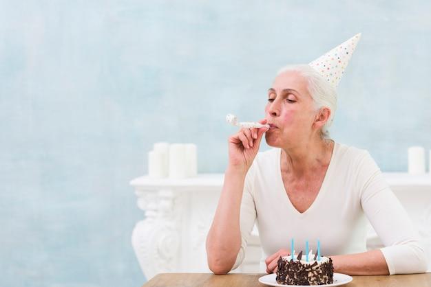 Mujer de cumpleaños senior que sopla fiesta cuerno en frente dulce pastel
