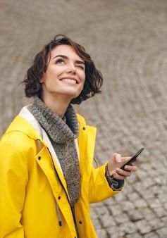 Mujer curiosa con cabello castaño rizado leyendo pronóstico en teléfono inteligente y mirando al cielo atornillando su ojo