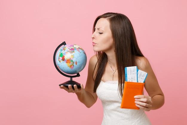 Mujer curiosa en vestido blanco mirando el globo terráqueo, sosteniendo pasaporte boleto de embarque, ir al extranjero, vacaciones