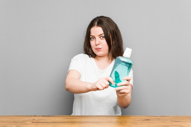 Mujer con curvas caucásica joven que limpia su boca con un enjuague bucal
