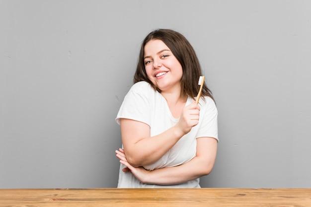 Mujer con curvas caucásica joven que limpia sus dientes con un cepillo de dientes aislado en una pared gris