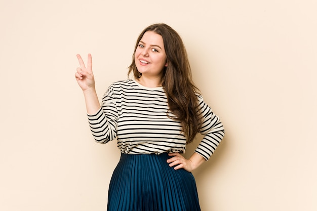 Mujer con curvas joven alegre y despreocupada que muestra un símbolo de paz con los dedos.