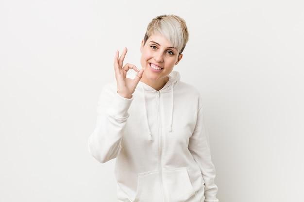 Mujer con curvas joven que lleva una sudadera con capucha blanca alegre y confiada que muestra gesto aceptable.