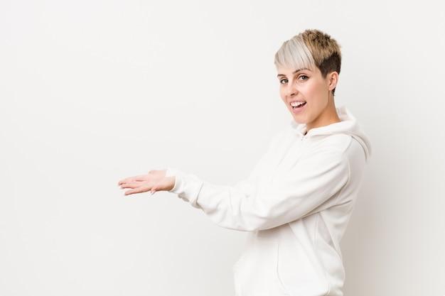 Mujer con curvas joven que llevaba una sudadera con capucha blanca con un espacio de copia en una palma.