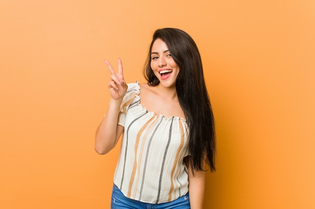 Mujer con curvas joven que muestra la muestra de la victoria y que sonríe ampliamente.
