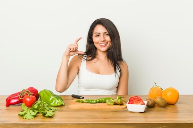 Mujer con curvas joven que prepara una comida sana que lleva a cabo algo poco con los índices, sonriendo y confiado.