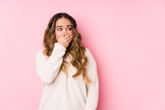 Mujer con curvas joven que presenta en una pared rosada aislada pensativa mirando a un espacio de la copia que cubre la boca con la mano.