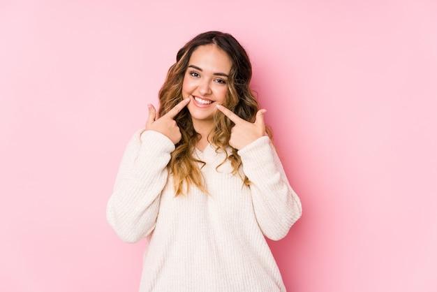 La mujer con curvas joven que presenta en una pared rosada sonríe aislada, señalando los dedos en la boca.