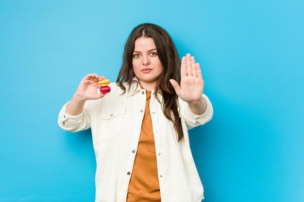Mujer con curvas joven que sostiene los macarrones que se colocan con la mano extendida que muestra la señal de stop, previniéndole.