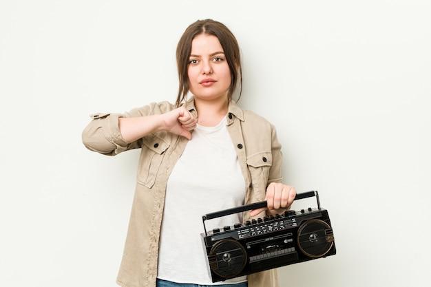 Mujer con curvas joven que sostiene una radio retra que muestra un gesto de la aversión, pulgares abajo. concepto de desacuerdo