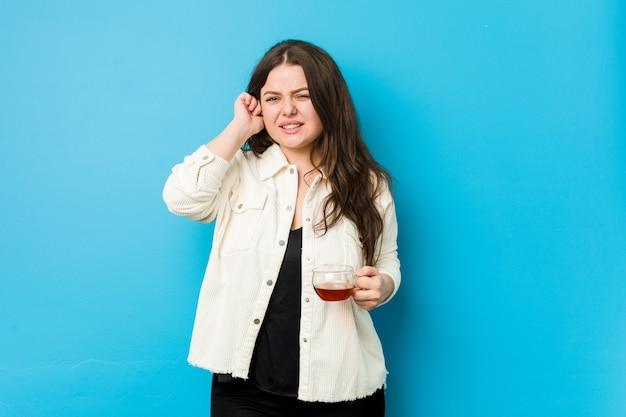 Mujer con curvas joven que sostiene una taza de té que cubre los oídos con las manos.