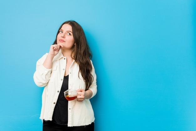 Mujer con curvas joven que sostiene una taza de té que mira de lado con expresión dudosa y escéptica.