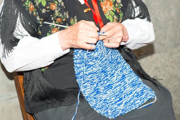La mujer se da cuenta de un suéter de lana con agujas.