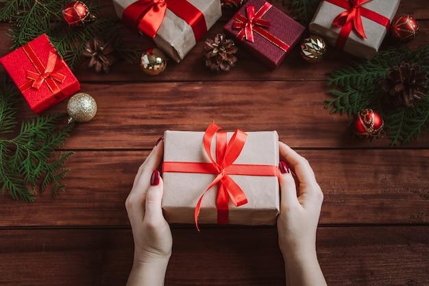 Mujer da hermosa caja de regalo con lazo rojo. concepto de navidad.