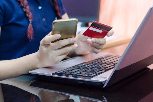 La mujer da sostener la tarjeta de crédito usando en el teléfono y el ordenador portátil elegantes.
