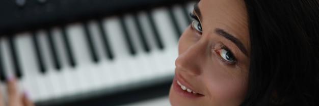 Mujer se da vuelta mientras toca el piano electrónico