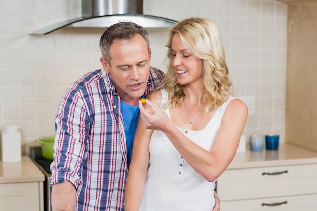 Mujer dando algo de comer a su marido en la cocina