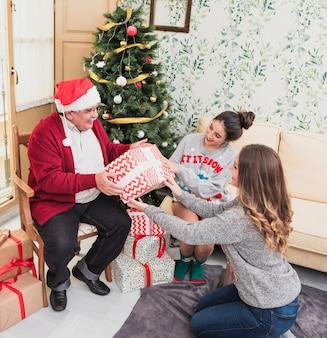 Mujer dando caja de regalo a anciano.