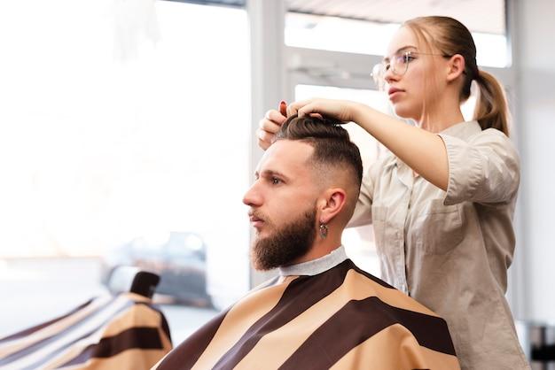 Mujer dando un corte de pelo a un cliente