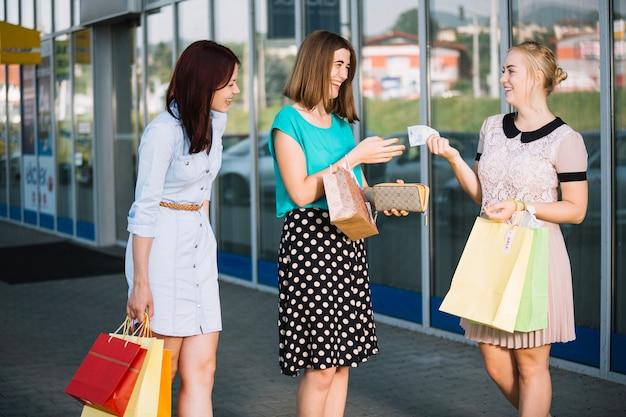Mujer dando dinero a un amigo