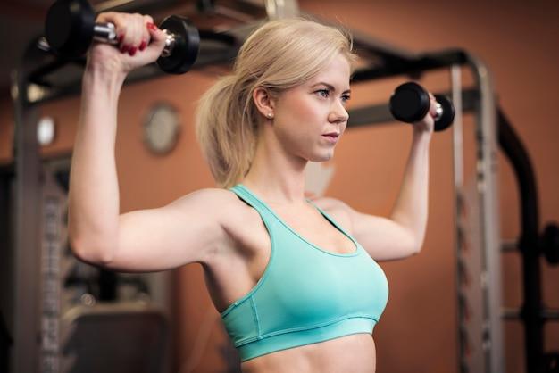 Mujer dando forma a sus hombros en el gimnasio