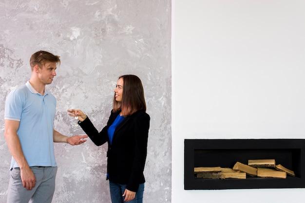 Mujer dando un juego de llaves a un hombre
