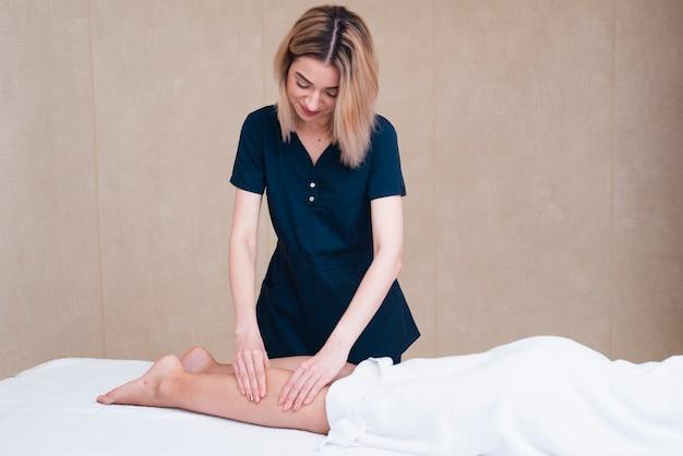 Mujer dando masaje de pies en el spa