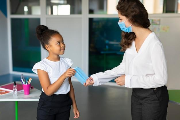 Mujer dando una mascarilla médica a un estudiante