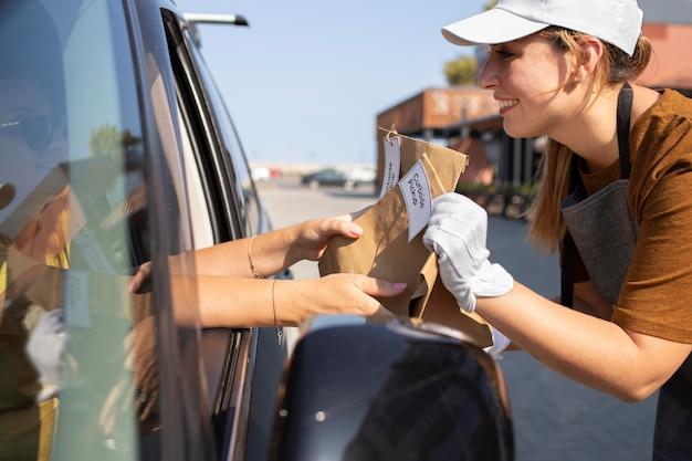 Mujer dando una orden en una camioneta en la acera exterior