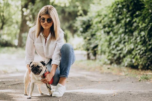 Mujer dando un paseo en el parque con su mascota perro pug