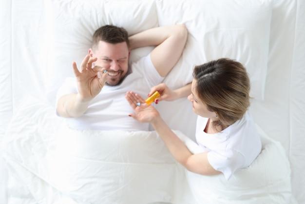 Mujer dando píldora al hombre en la cama vista superior