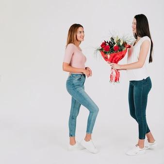 Mujer dando ramo de flores a la novia