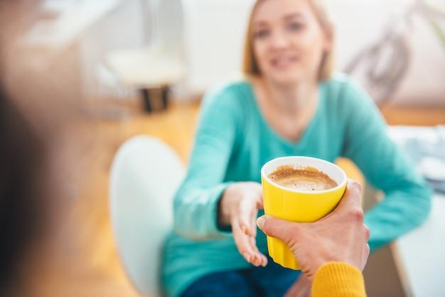 Mujer dando taza de café a su colega