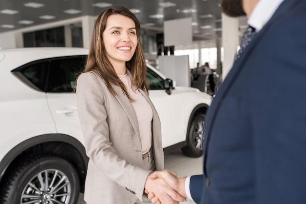 Mujer dándose la mano con el vendedor de autos