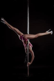 Mujer de danza del poste delgado joven sobre un fondo negro de estudio