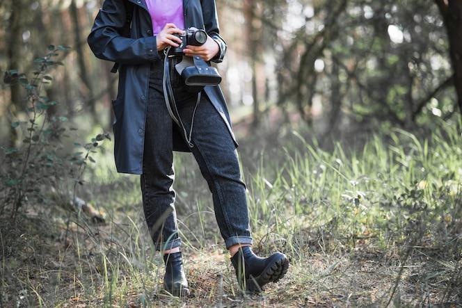 Mujer de cultivo con cámara en el bosque