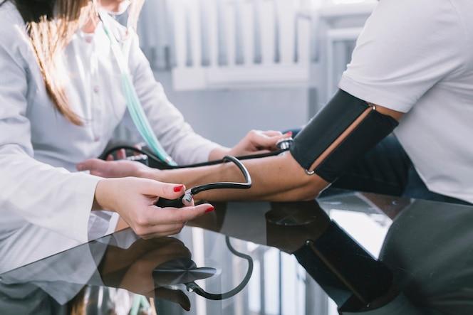 Mujer de cultivo medir pulso al paciente