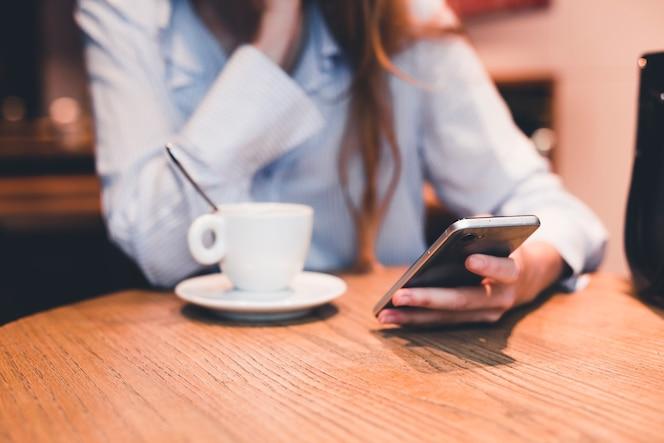 Mujer de cultivo navegando teléfono inteligente en café