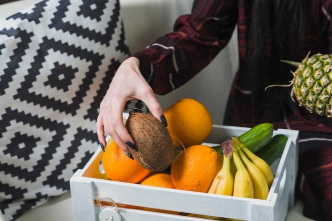 Mujer de cultivo tomando frutas de la caja de madera