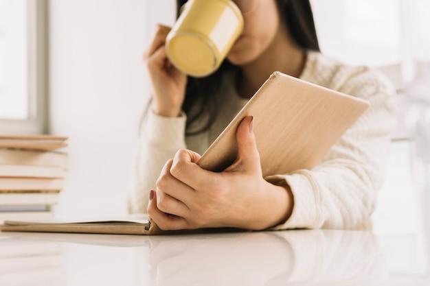 Mujer de cultivos bebiendo y leyendo en la mesa